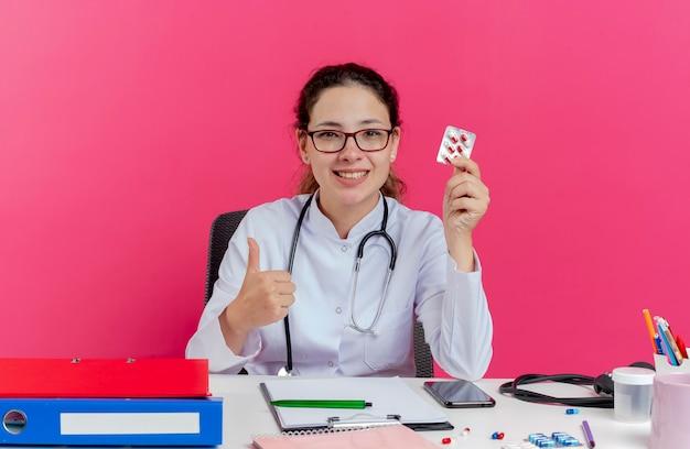 Lächelnde junge ärztin, die medizinische robe und stethoskop und brille trägt, die am schreibtisch sitzen