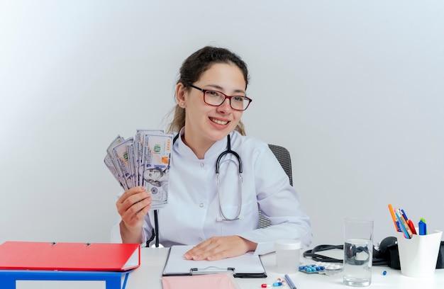Lächelnde junge ärztin, die medizinische robe und stethoskop und brille trägt, sitzt am schreibtisch mit medizinischen werkzeugen, die geld halten, das seite lokalisiert betrachtet
