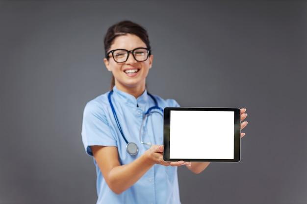 Lächelnde junge ärztin in uniform, mit stethoskop um den hals stehend und tablette zeigend.