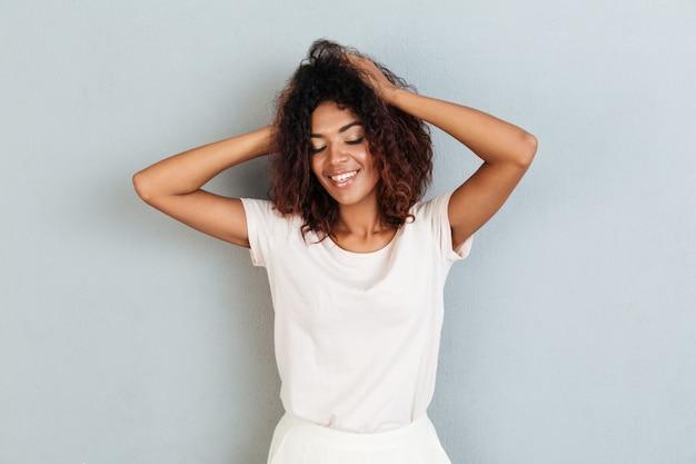 Lächelnde junge afrikanische frau, die über graue wand steht.