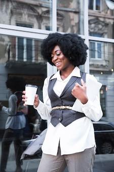 Lächelnde junge afrikanische geschäftsfrau, die in der hand mitnehmerkaffeetasse und digitale tablette hält