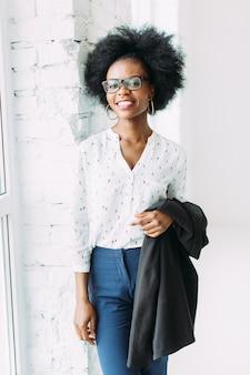 Lächelnde junge afroamerikanische geschäftsfrau, die eine jacke, stehend nahe dem großen fenster hält
