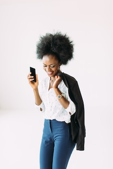 Lächelnde junge afroamerikanische geschäftsfrau, die handy verwendet