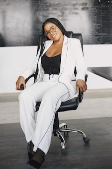 Lächelnde junge afroamerikanische geschäftsfrau, die in einem büro arbeitet. geschäftskonzept.