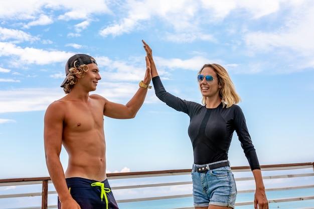 Lächelnde junge aktive paar-surfer, die auf dem strand nach sport sich entspannen