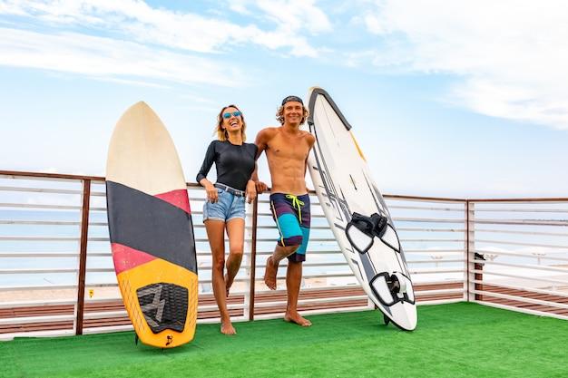 Lächelnde junge aktive paarsurfer, die auf dem strand nach sport mit surfbrett sich entspannen. gesunder lebensstil. extremer wassersport
