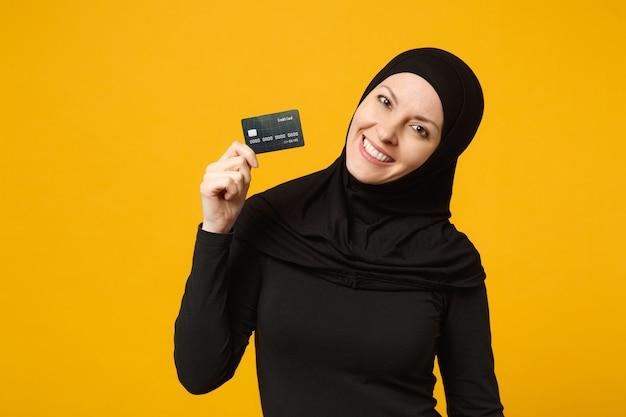 Lächelnde junge arabische muslimische frau des spaßes in der schwarzen kleidung des hijab halten in der hand kreditkarte, die auf gelbem wandporträt lokalisiert wird. menschen religiöses lifestyle-konzept.