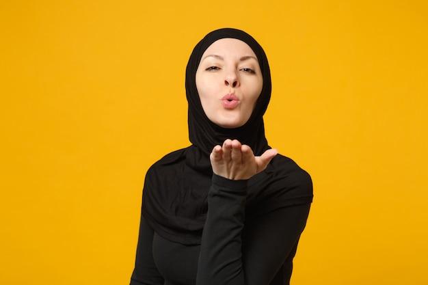 Lächelnde junge arabische muslimische frau in hijab schwarzer kleidung bläst luftkuss, isoliert auf gelber wand, porträt. menschen religiöses lifestyle-konzept.