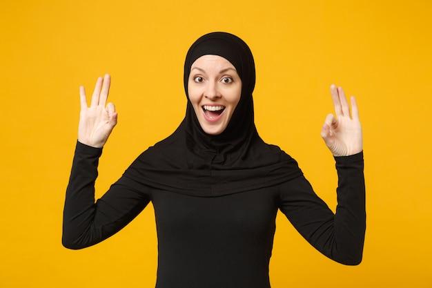 Lächelnde junge arabische muslimische frau in hijab-schwarzer kleidung, die ok-geste einzeln auf gelber wand, porträt zeigt. menschen religiöses lifestyle-konzept.