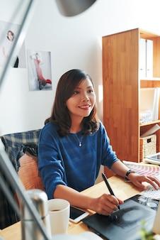 Lächelnde junge asiatin in blauem pullover, die am schreibtisch sitzt und den digitizer verwendet, während sie computergrafiken erstellt