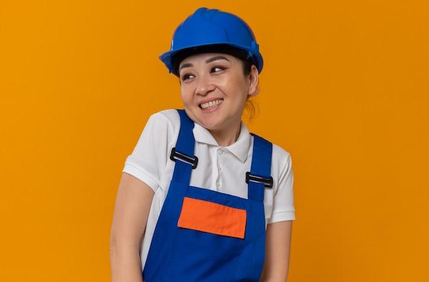Lächelnde junge asiatische baumeisterin mit blauem schutzhelm, der auf die seite schaut