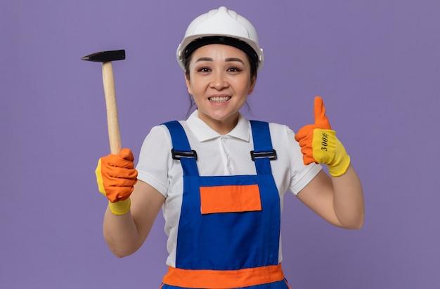 Lächelnde junge asiatische baumeisterin mit weißem schutzhelm und handschuhen, die hammer halten und hochdrücken
