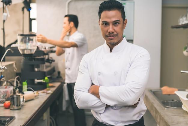 Lächelnde junge asiatische chef in der küche interieur.