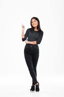 Lächelnde junge asiatische dame, die isoliert steht und auf copyspace zeigt.