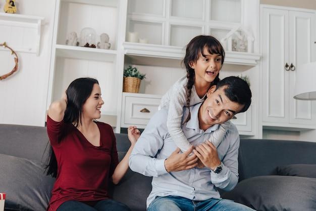 Lächelnde junge asiatische eltern und ihr kind sind sehr glücklich, sie sind zu hause