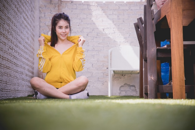 Lächelnde junge asiatische frau, die auf grünem gras, konzept des asiatischen frauenlebensstils sitzt.