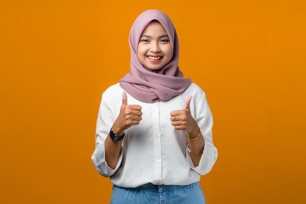 Lächelnde junge asiatische frau, die daumen auf gelb macht