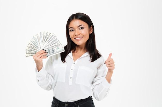 Lächelnde junge asiatische frau, die geld hält, das daumen hoch zeigt.