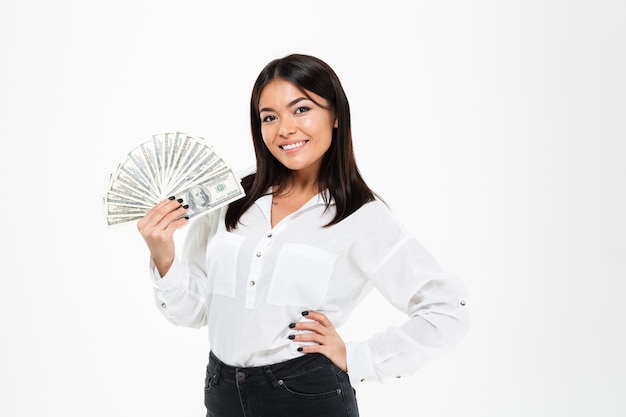 Lächelnde junge asiatische frau, die geld hält.