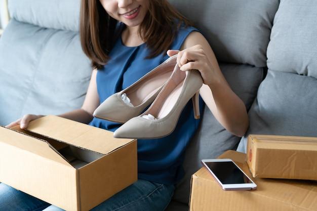 Lächelnde junge asiatische frau, die ihren neuen schuh mit hohen absätzen betrachtet und zu hause auf sofa sitzt, digitaler lebensstil mit technologie, e-commerce, online-shopping-konzept