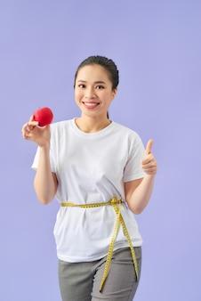 Lächelnde junge asiatische frau, die maßband um ihre taille hält und roten apfel über violettem hintergrund isst