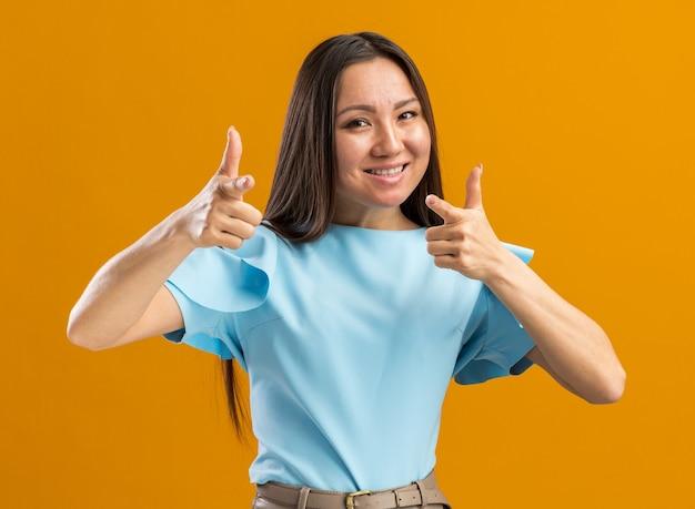 Lächelnde junge asiatische frau, die nach vorne auf orangefarbene wand isoliert schaut und zeigt