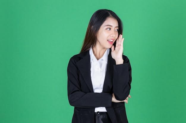 Lächelnde junge asiatische geschäftsfrau mit hand über ohr
