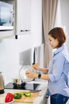 Lächelnde junge asiatische hausfrau, die kochende suppe im topf mischt