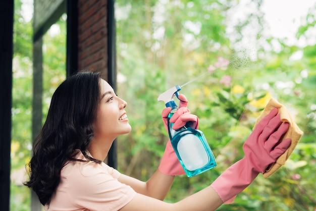 Lächelnde junge asiatische hausfrau wäscht ein fenster