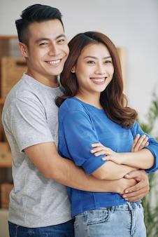 Lächelnde junge asiatische paare, die zuhause stehen und umarmen