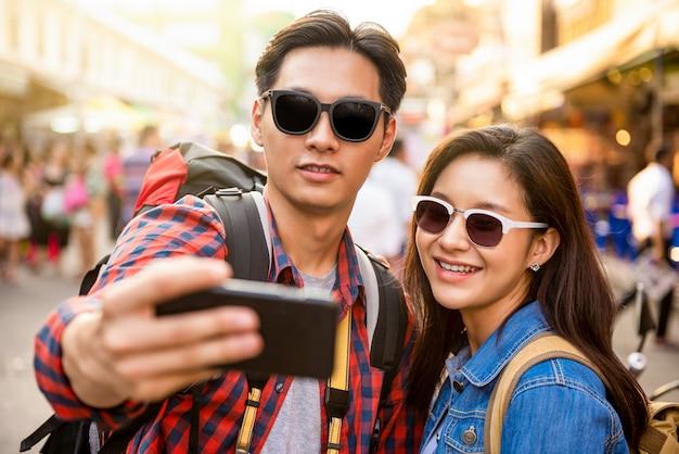 Lächelnde junge asiatische paartouristen, die selfie nehmen, während sie in den sommerferien in khao san straße bangkok thailand reisen