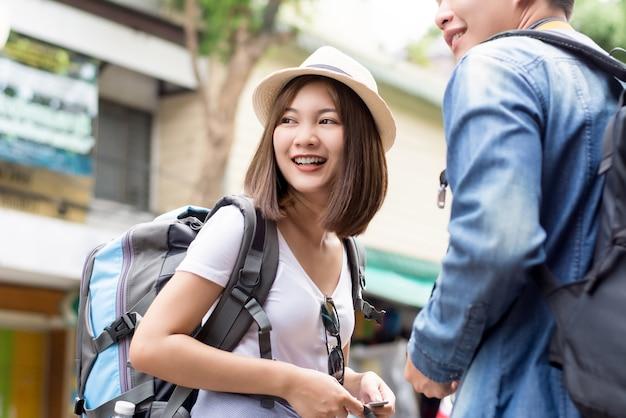 Lächelnde junge asiatische paartouristenwanderer