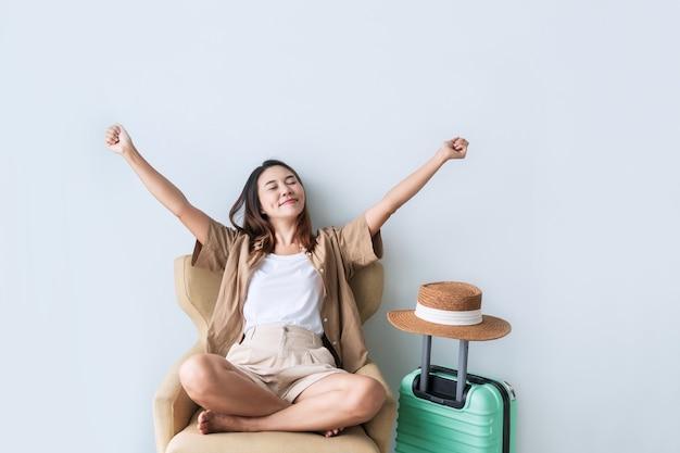 Lächelnde junge asiatische reisende frau, die auf couch sitzt, während sie ihre hände mit glücksgeste auf hotelzimmer hob. alleine reisen, sommer- und urlaubskonzept. nahansicht