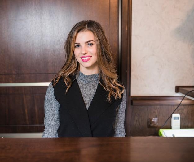 Lächelnde junge attraktive frau, die am schreibtisch im hotel sitzt