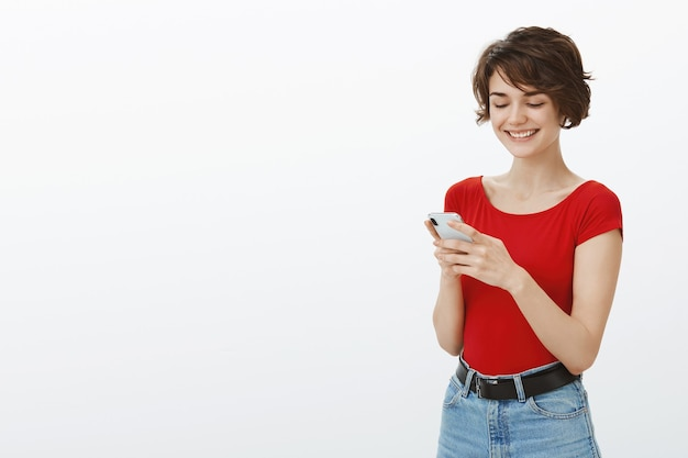 Lächelnde junge attraktive frau sms auf handy, mit dating-app auf smartphone