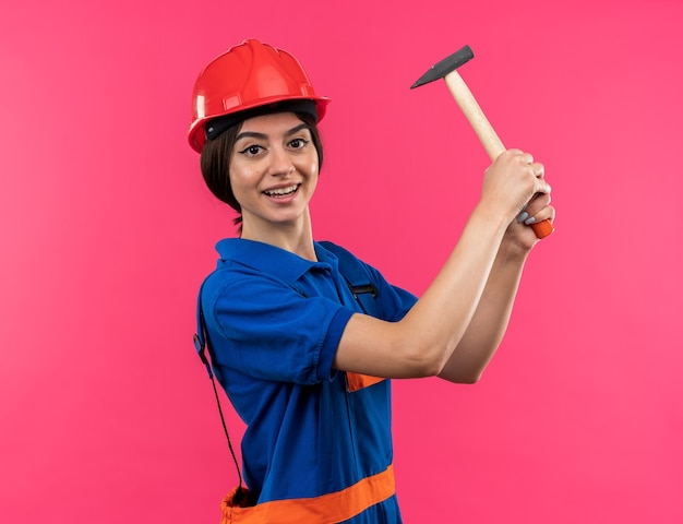 Lächelnde junge baumeisterin in uniform, die den hammer anhebt