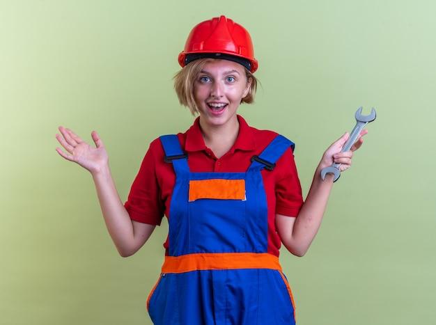 Lächelnde junge baumeisterin in uniform, die einen gabelschlüssel hält, der die hände isoliert auf der olivgrünen wand ausbreitet