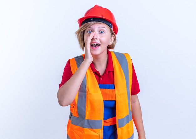 Lächelnde junge baumeisterin in uniform, die jemanden anruft, der auf weißer wand isoliert ist?