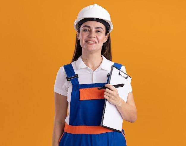 Lächelnde junge baumeisterin in uniform, die zwischenablage mit stift lokalisiert auf orange wand hält
