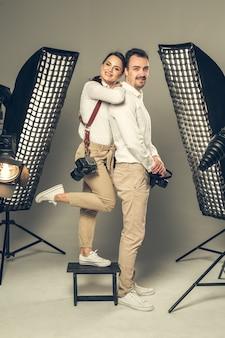 Lächelnde junge berufsfotografen, die im studio aufwerfen