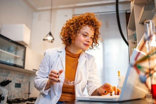 Lächelnde junge biochemikerin mit laptop an ihrem schreibtisch im labor.
