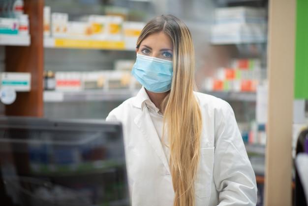 Lächelnde junge blonde apothekerin mit covid coronavirus-maske in ihrer apotheke