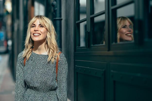Lächelnde junge blonde frau, die auf städtischem hintergrund steht.