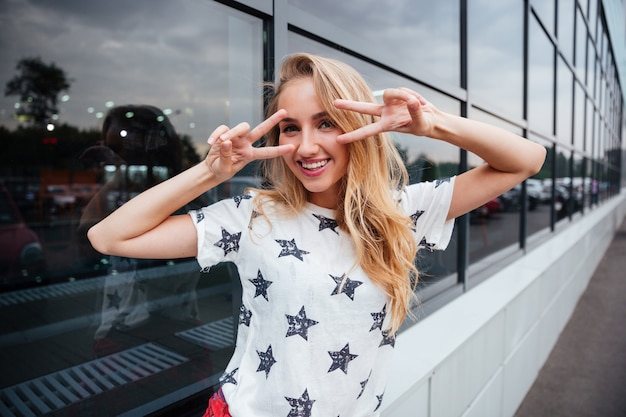 Lächelnde junge blonde frau, die v-zeichen zeigt, während sie draußen am glasgebäude steht