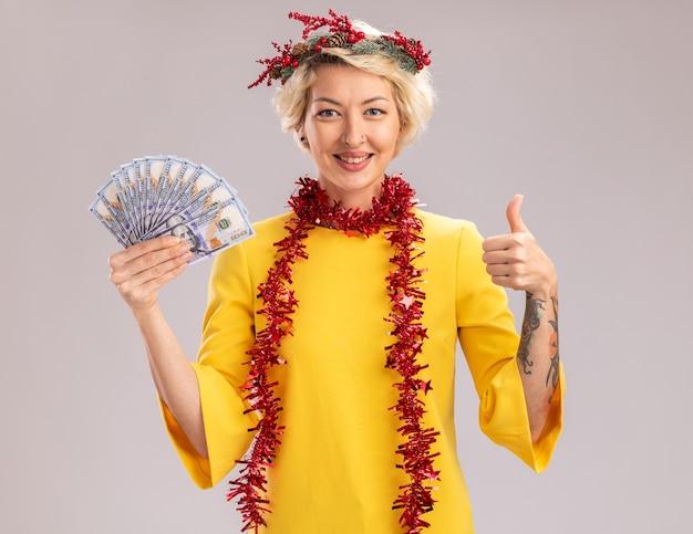 Lächelnde junge blonde frau, die weihnachtskopfkranz und lametta-girlande um den hals hält, der geld betrachtet, das kamera betrachtet daumen oben auf weißem hintergrund zeigt