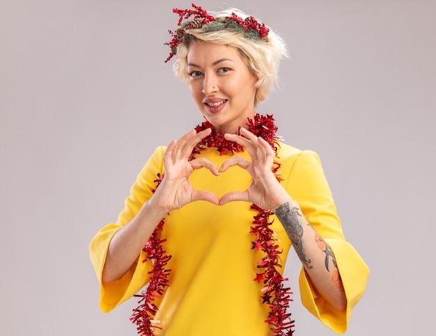 Lächelnde junge blonde frau, die weihnachtskopfkranz und lametta-girlande um den hals trägt und kamera betrachtet, die herzzeichen lokalisiert auf weißem hintergrund tut