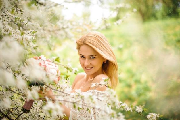 Lächelnde junge blonde frau im weißen kleid mit einem blumenstrauß nahe dem blühenden kirschbaum