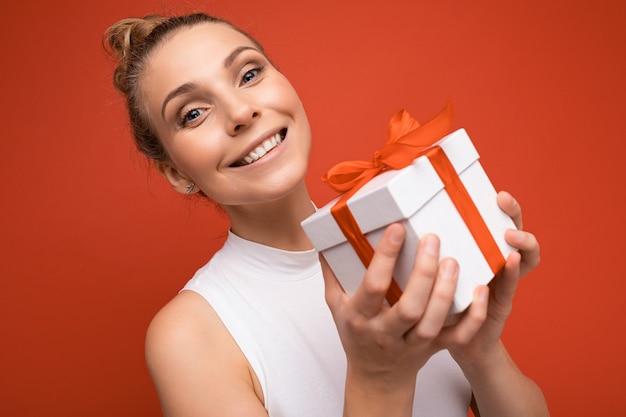 Lächelnde junge blonde frau lokalisiert über bunte hintergrundwand, die alltägliches trendiges outfit hält, das geschenkbox hält und kamera betrachtet.