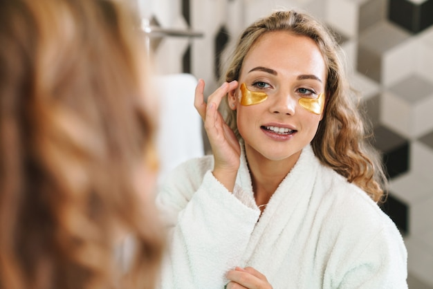 Lächelnde junge blonde frau mit bademantel, die kosmetische augenklappen anwendet, während sie am badezimmerspiegel steht
