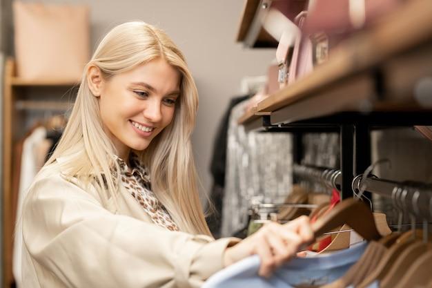 Lächelnde junge blonde frau mit langen haaren, die durch neue modekollektion auf gestell schaut, während sie neues sweatshirt oder pullover wählt